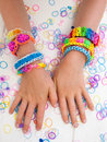 Childs arms wearing multicoloured bracelets colourful elastic loom band worn on a child hands against a white table top Stock Image