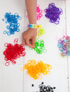 Childs hand and coloured elastic bands picking a band from a table top with piles of colourful Royalty Free Stock Photography