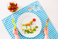 Childs hand and healthy vegetable lunch vegetarian for little kids vegetables fruit served as animals corn broccoli carrots fresh Stock Photo