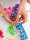 Childs hands and band loom hand placing coloured elastic bands on a with white table top coloured elastics behind Stock Images