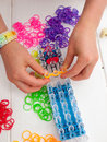 Childs hands and band loom hand placing a coloured elastic on a with white table top coloured elastics behind Royalty Free Stock Photo
