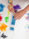 Childs hands with croche hook and band loom hand hooking coloured elastic bands on a white table top coloured elastics behind Stock Images
