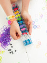 Childs hands making a multicoloured elastic band bracelet on a b braclet with colourful loom bands loom against white table top Stock Photos