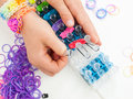 Childs hands making a multicoloured elastic band bracelet on a b closeup of braclet with colourful loom bands loom against white Stock Images