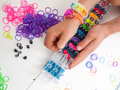 Childs hands making a multicoloured elastic band bracelet on a b closeup of braclet with colourful loom bands loom against white Royalty Free Stock Photography