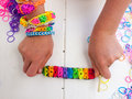 Childs hands showing multicoloured bracelet colourful elastic loom band held in a child against a white table top Royalty Free Stock Photo
