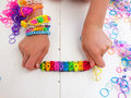 Childs hands showing multicoloured bracelets colourful elastic loom band bracelet held in a child against a white table top Royalty Free Stock Image