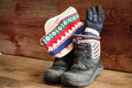 Childs snow boots with a winter cap and gloves colorful knitted thick warm standing ready in rustic wooden cabin to venture out Stock Photos