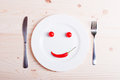 Chili cherry tomatoes in the form of a smiling smiley on a white Royalty Free Stock Photo