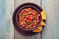 Chili con carne in bowl with tortilla chips on wooden background Royalty Free Stock Images