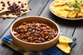 Chili con carne with homemade tortilla chips wooden bowl of in the back photographed natural light selective focus focus in Royalty Free Stock Photography