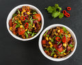 Chili con carne in a white ceramic bowl on black stone background. Cooked with ground beef, tomatoes, peppers, beans, corn, garlic Royalty Free Stock Photo