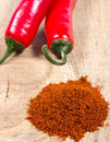 Chili peppers and chili powder on a wooden background Royalty Free Stock Photo