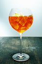 Chilled aperol spritz tropical rum and orange cocktail in an elegant wine glass standing on a wooden counter in a bar or club Stock Photo