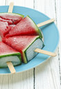 Chilled watermelon with ice cream sticks on white wooden background Stock Photo