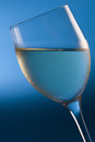 Chilled white wine a glass of helpd at an angle against a gradient blue background Royalty Free Stock Photo