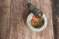 Chilli pepper in stone mortar on the wooden table Royalty Free Stock Photo