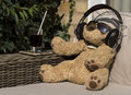 Chilling with music cuddly toy in sunshine listening to Royalty Free Stock Photo