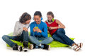 Chilling teenagers three on a green beanbag lisiting to some music and using there mobile phones Royalty Free Stock Images