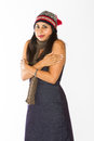 Chilly indian woman an in a blue dress poses in front of a white background wearing a stocking hat and scarf Royalty Free Stock Images