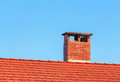 Chimney red tiles roof with and blue sky in the background Royalty Free Stock Photos