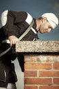 Chimney sweep man checking chimney in work uniform cleaning brick style on building roof Stock Image