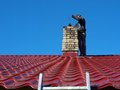 Chimney sweep man with special wire brush on roof clean Stock Photos