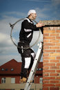 Chimney sweep man in work uniform cleaning brick style on building roof Stock Photos