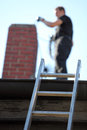 Chimney sweep at work on a roof with a ladder balanced against the guttering and focus to the ladder Royalty Free Stock Photos