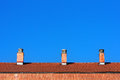 Chimneys on house roof against blue sky Royalty Free Stock Photo