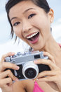 Chinese asian girl woman at beach taking photographs young laughing vacation photograph in a bikini the using a digital camera Stock Photography