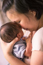 Chinese asian malaysian mother and her newborn infant baby boy embracing Stock Image