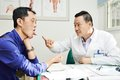 Chinese asian male doctor at work adult in clinic during tongue diagnosis Royalty Free Stock Images