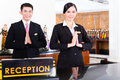 Chinese asian reception team at hotel front desk luxury welcoming guests with typical gesture a sign of good service and Royalty Free Stock Photo
