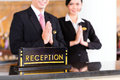 Chinese asian reception team at hotel front desk luxury welcoming guests with typical gesture a sign of good service and Stock Image