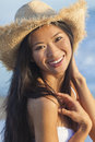 Chinese asian woman girl bikini cowboy hat beach outdoor portrait of a beautiful young or wearing a white and straw at a Stock Image
