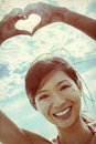 Chinese asian woman girl hand heart finger frame beautiful young smiling on a beach in a bikini making a shaped photograph Stock Photos