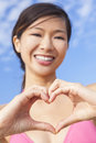 Chinese asian woman girl making heart hands shape beautiful happy young or in a pink bikini a symbol with her Stock Images