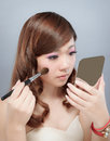 Chinese beauty applying make up with professional makeup with brush in photography studio Stock Image