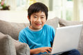 Chinese Boy Using Laptop Sitting On Sofa At Home Royalty Free Stock Images