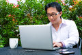 Chinese businessman working outdoor asian he is with laptop and checking emails Stock Photos