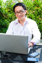 Chinese businessman working outdoor asian he is with laptop and checking emails Stock Photo