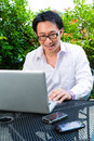 Chinese businessman working outdoor asian he is with laptop and checking emails Royalty Free Stock Photography