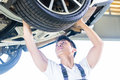 Chinese car mechanic changing auto tire Royalty Free Stock Photo