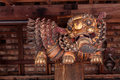 Chinese carving wooden lion decorated by stick to pillar Royalty Free Stock Photo