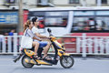 Chinese couple on an electric bike o Stock Photos