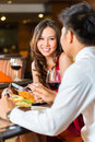 Chinese couple having romantic dinner in fancy restaurant asian man and women or lovers flirting and a date or a Royalty Free Stock Photo