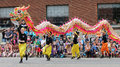 Chinese dragon in a parade men belonging to kung fu club run through the streets with during the k days klondike days summer Royalty Free Stock Photography