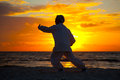 Chinese elderly woman performing taichi outdoor morning by the beach under sunset sunrise silhouette Stock Image