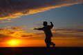 Chinese elderly woman performing taichi outdoor morning by the beach under sunset sunrise silhouette Stock Photo